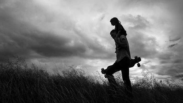 silhouette portrait of dad and son walking at the field